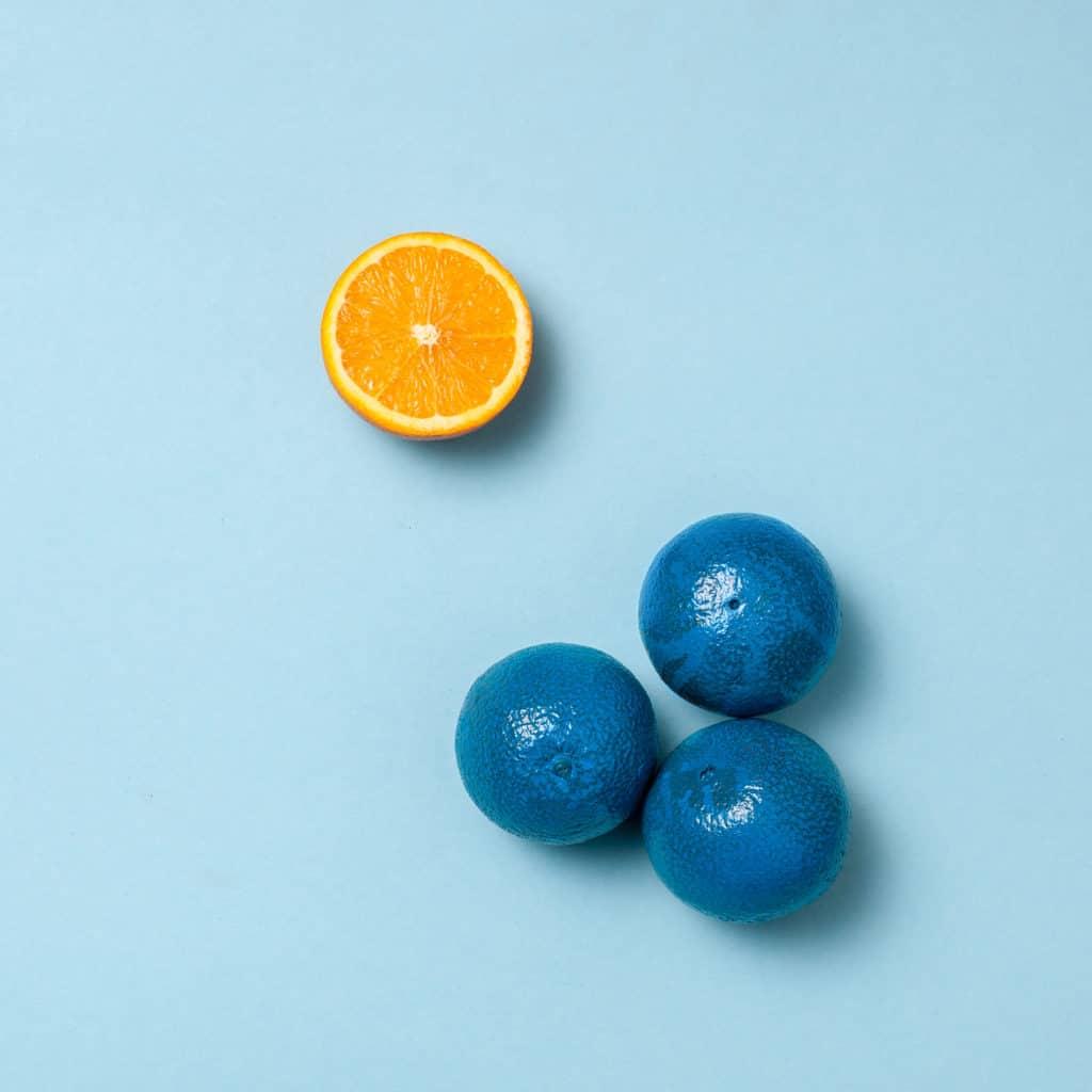 blue oranges with one half orange apart