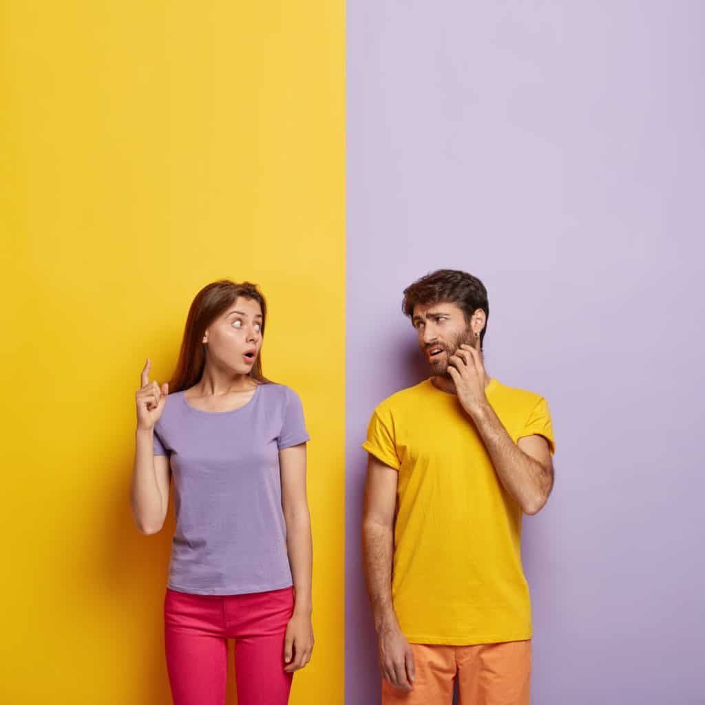 photo emotional impressed woman tries explain something man points with shocked expression displeased guy scratches bristle wears yellow t shirt